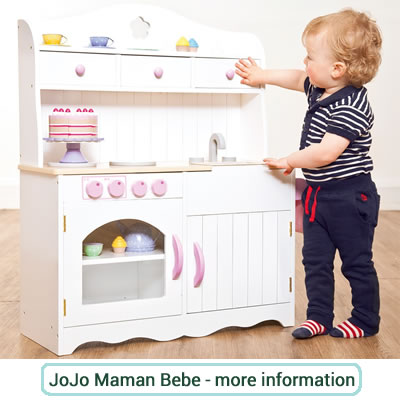 Small, white wooden play kitchen with pink knobs and door handles.